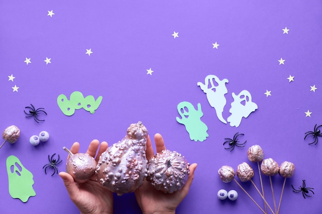 Halloween flat lay on purple background with paper ghosts, spiders, stars and chocolate candy eyes
