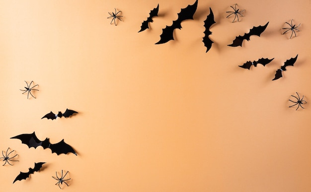 Halloween flat lay with decorations made from paper bats and black spider