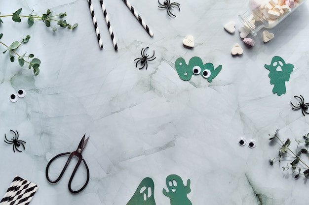 ハロウィーンフラットユーカリ、シュガーハートキャンディー、黒いプラスチックのクモ、はさみ、紙の幽霊のシルエット、単語ブー、コピースペースで横たわっていた。