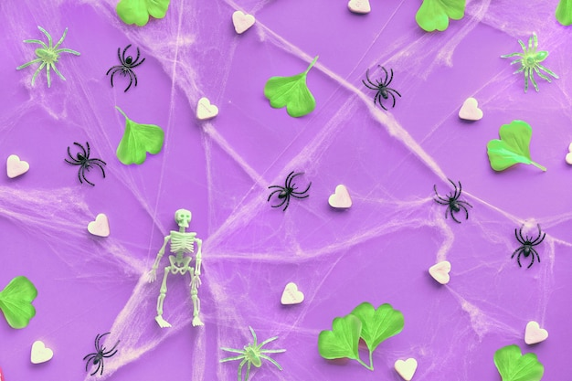 Halloween flat lay with neon green ginkgo leaves, spider web and black spiders on vibrant purple paper.