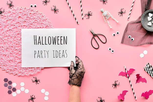 Halloween flat lay with scissors and decorations on pink paper background. hexagon confetti, paper drink straws, bats and spiders.