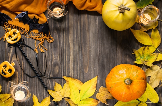 Halloween flat lay on wooden background with pumpkins, autumn leaves and candles