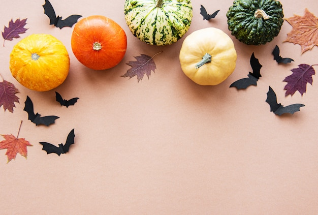 Halloween flying bats and pumpkins on brown background