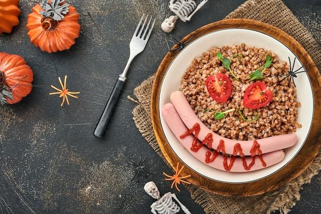할로윈 음식 예술 아이디어 아이들을 위한 건강한 점심. 삶은 메밀 죽, 고기 소시지, 토마토, 완두콩의 마이크로그린을 하얀 접시에 담아 아이들의 아침 식사나 돌 배경의 점심을 제공합니다. 평면도.