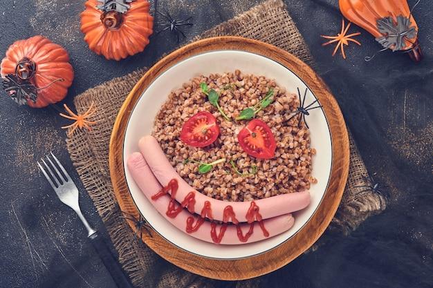 아이들을 위한 할로윈 음식 예술 아이디어 건강한 점심. 삶은 메밀 죽, 고기 소시지, 토마토, 완두콩의 마이크로그린을 하얀 접시에 담아 아이들의 아침 식사나 돌 배경의 점심을 제공합니다. 평면도.
