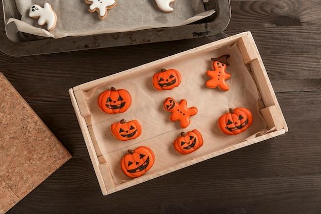 Концепция еды хэллоуина. забавное оранжевое печенье в виде тыквы и человечков лежит в форме на столе. хэллоуин угощение