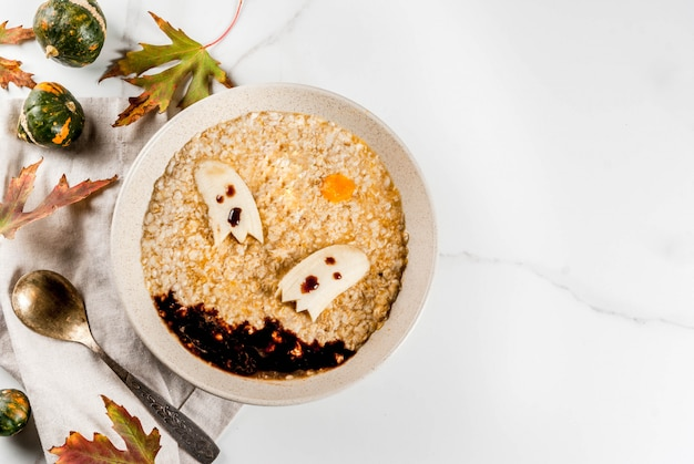 子供向けのハロウィーンフードレシピ、怖い食用バナナゴーストとチョコレートソースが付いた甘いカボチャオートミールの子供の朝食