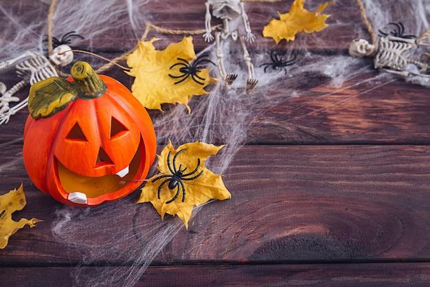 ハロウィンフレーム構成。オレンジ色のカボチャ、スケルトン、黄色の乾燥した葉、暗い木製の背景のウェブ上の黒いクモ。スペースをコピーします。フラットレイ。