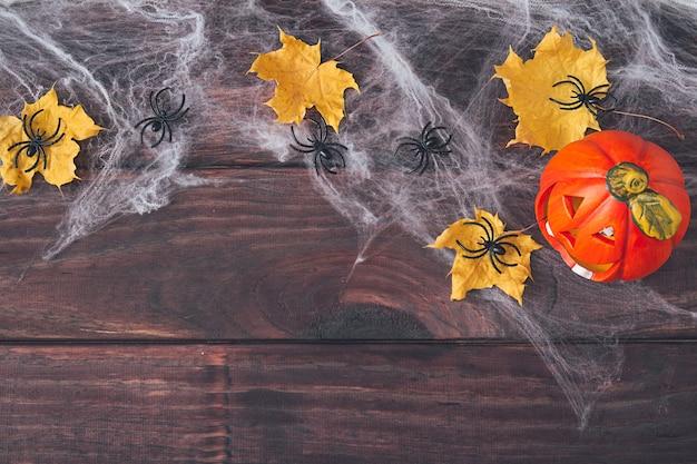 ハロウィンフレーム構成。オレンジ色のカボチャ、黄色の乾燥した葉、暗い木製の背景のウェブ上の黒いクモ。スペースをコピーします。フラットレイ。