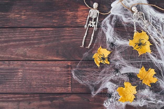 ハロウィンフレーム構成。スケルトン、黄色い乾燥した葉、暗い木製の背景のウェブ上の黒いクモ。スペースをコピーします。フラットレイ。