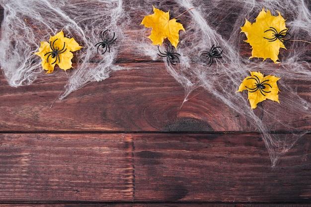 ハロウィンフレーム構成。黄色い乾燥した葉、暗い木製の背景にウェブ上の黒いクモ。スペースをコピーします。フラットレイ。