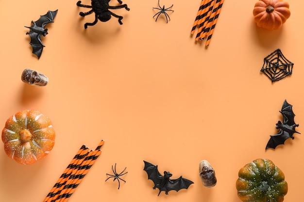 Halloween frame of fun party decorations, pumpkins, drinking straw, bat, skulls, spooky spider on orange background.