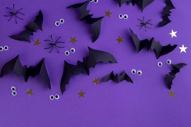 Шаблон рамки хэллоуина с черными бумажными летучими мышами и пластиковыми жуткими глазами на цветном фиолетовом фоне.
