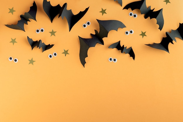 Шаблон рамки хэллоуина с черными бумажными летучими мышами и пластиковыми жуткими глазами на цветном желтом фоне.