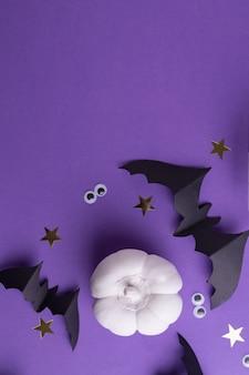 Шаблон рамки хэллоуина с черными бумажными летучими мышами, белыми декоративными тыквами и пластиковыми жуткими глазами на цветном фиолетовом фоне.