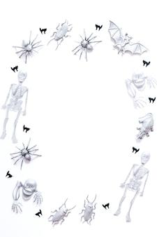 흰색 배경에 은색 박쥐, 해골, 거미, 검은 고양이 색종이 조각이 있는 할로윈 프레임, 복사 공간, 수직 이미지, 위쪽 보기