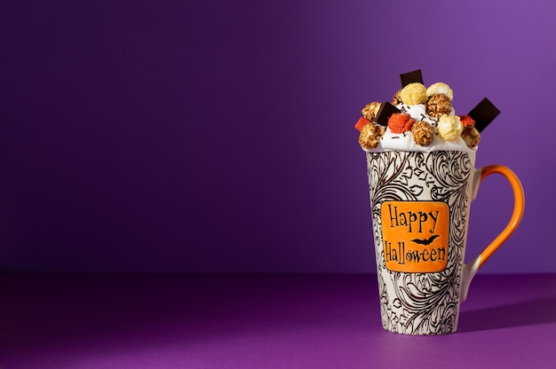 Halloween freak shake in tall mug on purple background with shadow. whipped cream with glazed popcorn, coloured marshmallow and chocolate. halloween background with copy space.