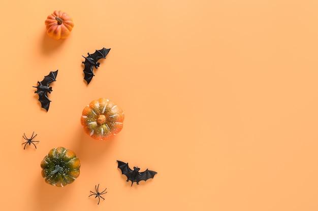 オレンジ色の背景にハロウィーンの楽しいパーティーの装飾、カボチャ、コウモリ、不気味なクモ。俯瞰図、フラットレイ。スペースをコピーします。