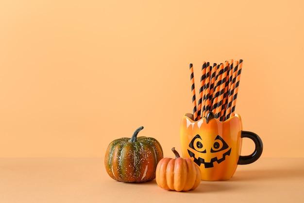 ハロウィーンの楽しいパーティーの装飾、カボチャ、オレンジ色の背景にストローとマグカップ。