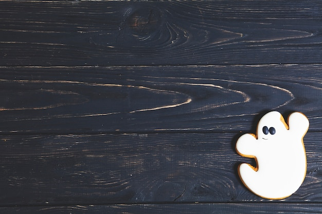 Halloween ghost cookie on black wooden table