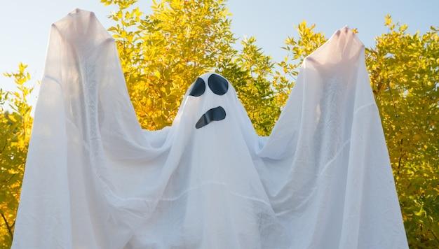 Призрак на хэллоуин танцует в осеннем желтом лесу, размахивая руками