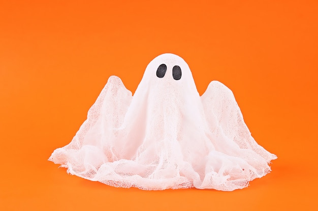 Halloween ghost of starch and gauze on orange background. gift idea, decor halloween.