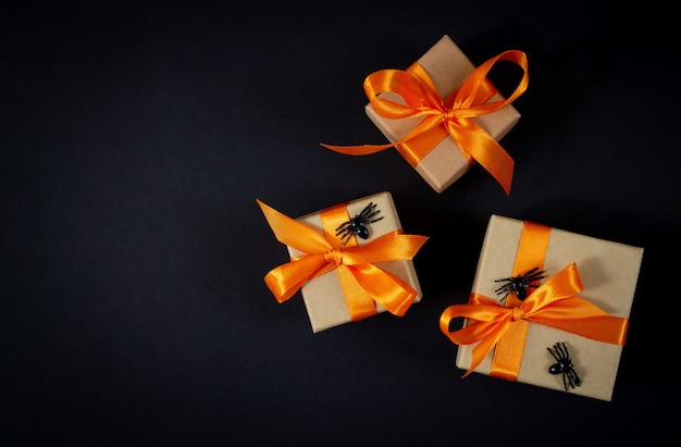 Halloween gift boxes with decorative spiders top view on dark background. space for your text