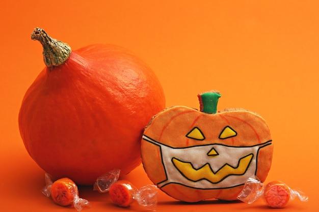 Halloween gingerbread cookie on orange background and pumpkin delicious biscuit for halloween