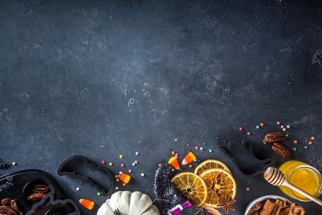 ハロウィーンジンジャーブレッドクッキー料理の背景。秋の休日のベーキングの概念、材料、スパイス、ハロウィーンのシンボルのクッキーカッター-カボチャ、ゴースト、バット、魔女の帽子、上面図の黒いテーブルのコピースペース