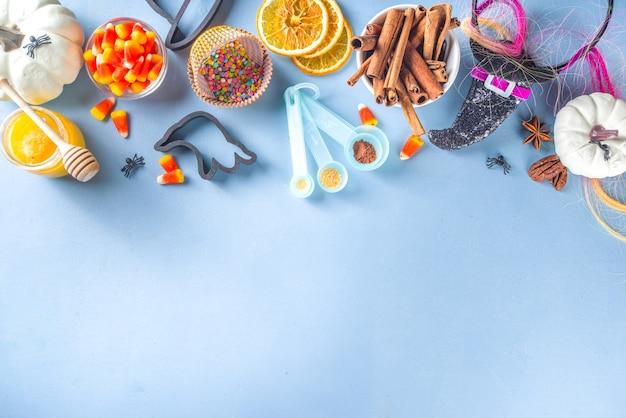 ハロウィーンジンジャーブレッドクッキー料理の背景。秋の休日のベーキングの概念、材料、スパイス、ハロウィーンのシンボルのクッキーカッター-カボチャ、ゴースト、バット、魔女の帽子、トップビューの青いテーブルのコピースペース