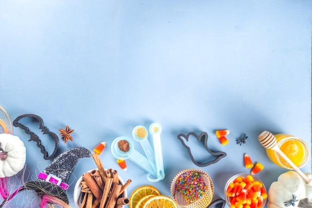 ハロウィーンジンジャーブレッドクッキー料理の背景。秋の休日のベーキングの概念、材料、スパイス、ハロウィーンのシンボルのクッキーカッター-カボチャ、ゴースト、バット、魔女の帽子、上面図青いテーブルのコピースペース