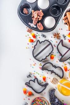 ハロウィーンジンジャーブレッドクッキー料理の背景。秋の休日のベーキングの概念、材料、スパイス、ハロウィーンのシンボルのクッキーカッター-カボチャ、ゴースト、バット、魔女の帽子、上面図の白いテーブルのコピースペース