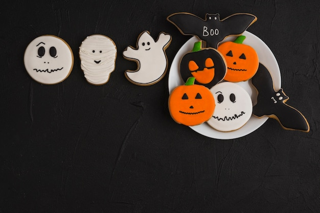 Halloween gingerbread on plate near white cookies