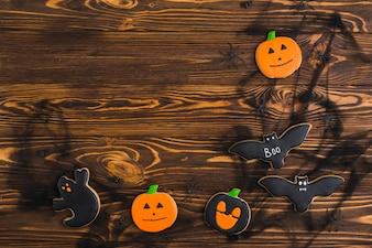 Halloween gingerbreads arranged on wood background