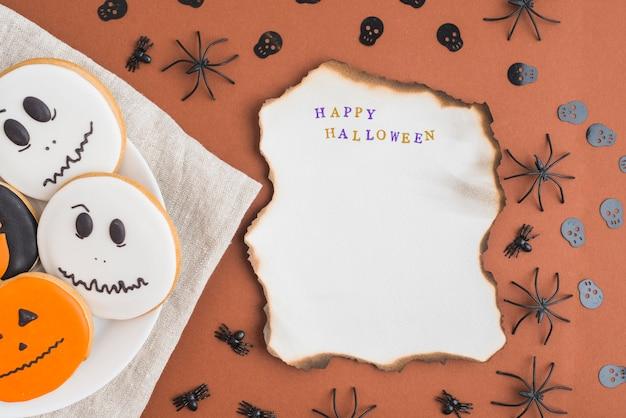 Halloween gingerbreads on dish near burning sheet