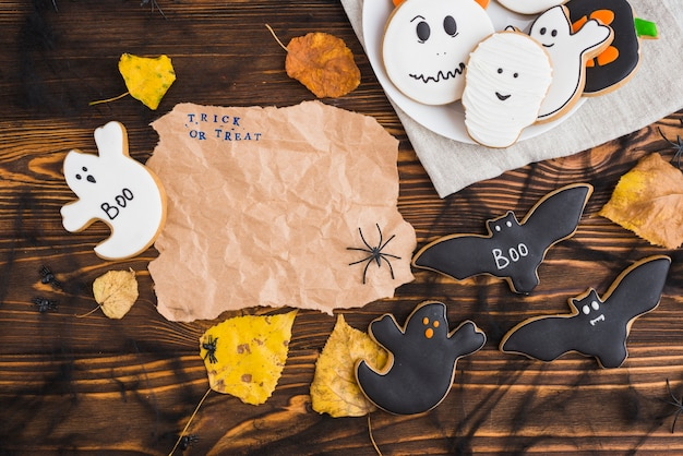 Halloween gingerbreads and leaves around craft paper