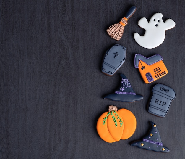 Halloween gingerbreads, pumpkin, ghost, witch hat, tombstone over dark wood background with copy space.