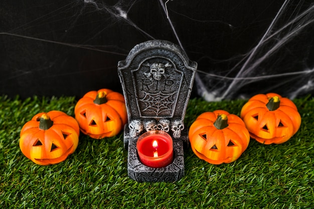 Halloween graveyard concept with pumpkins and candle
