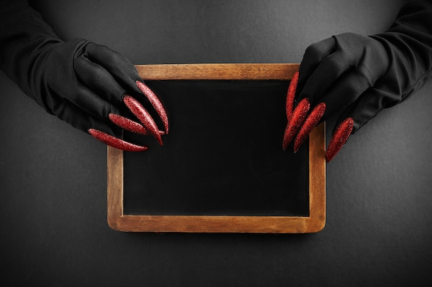 Halloween green witches or zombie monster hands holding desk