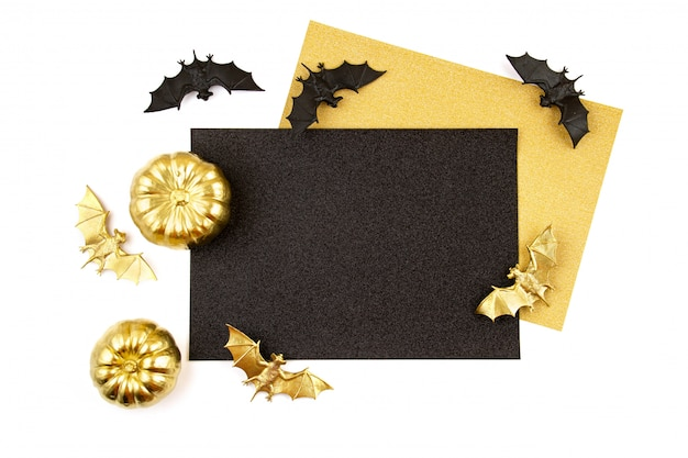 Halloween greeting card or invitation with golden pumpkin and party objects, bats, overhead view