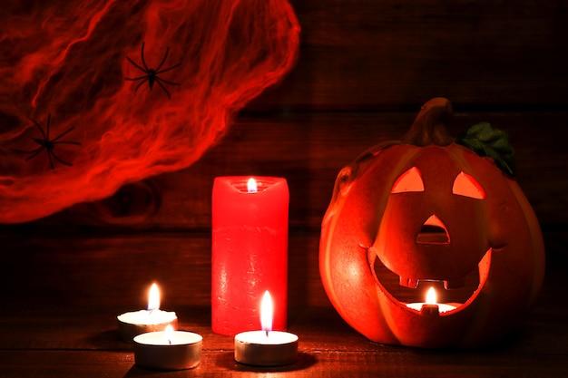 Открытка на хэллоуин с джек-о-лампой, свечами и паутиной с двумя пауками. выборочный фокус