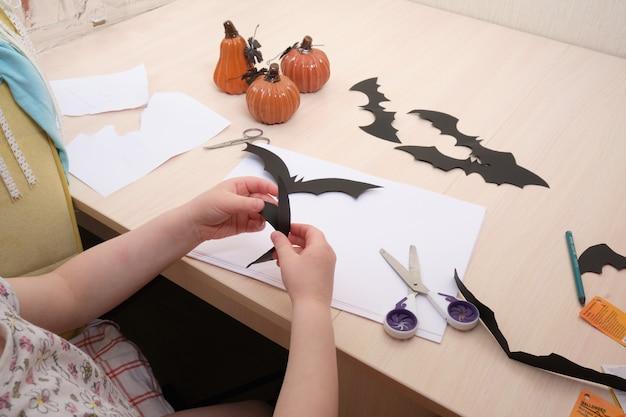 Хеллоуин декор ручной работы. ребенок вырезает летучую мышь из черной бумаги
