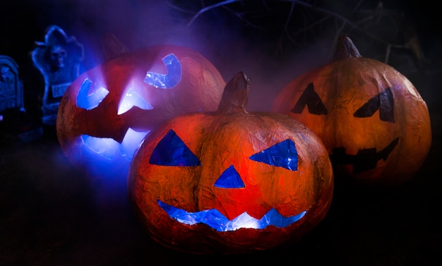 Halloween handmade pumpkins with carved illuminated faces and headstones behind