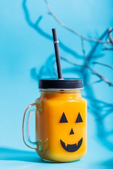 Halloween healthy pumpkin or carrot and tomato drinks in the glass jar with scary face on a blue background