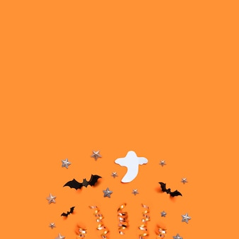 Halloween holiday background with bats, ghost, stars and decorations on an orange board.