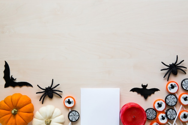 Halloween holiday background with spiders, bats, candies and pumpkins on wood