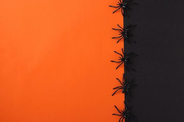 Заготовка праздника хеллоуина с черными пауками, черным и оранжевым космосом. плоская планировка, вид сверху. место для текста.