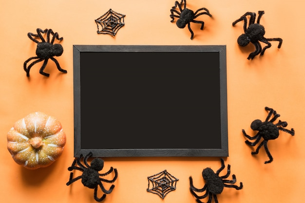 Halloween holiday blank with party decor, black spiders, web on orange. flat lay, top view. copyspace