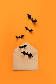 Halloween holiday composition of black bats fly out of craft paper envelope