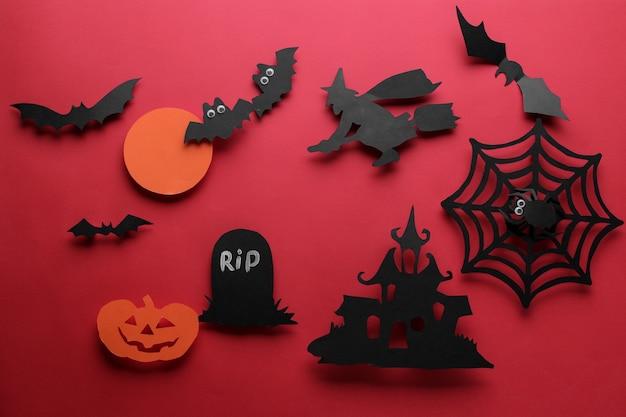 ハロウィーンの休日。さまざまなハロウィンの紙のフィギュアで構成。上からの眺め。赤い背景に